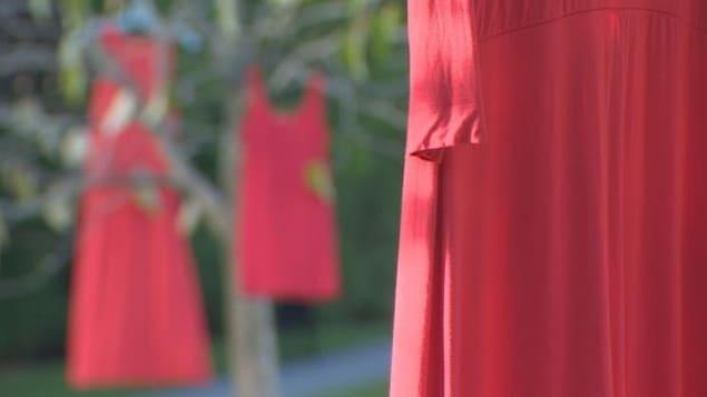 Des robes rouges sont suspendues aux arbres du parc Seaforth Peace à Vancouver pour souligner la Journée nationale d'action en faveur des femmes autochtones assassinées et disparues.
