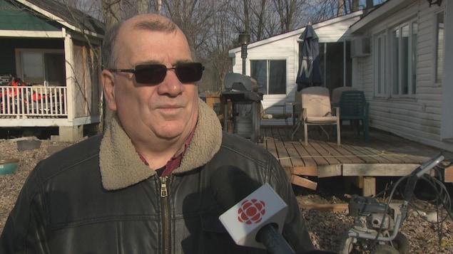 Robert Bergeron, un sinistré de municipalité de Pontiac, devant des maisons lors d'une entrevue.