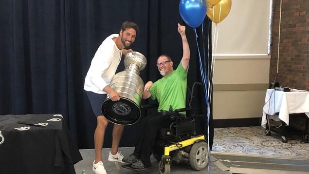 Un homme tient un trophée à côté d'une personne en fauteuil roulant.