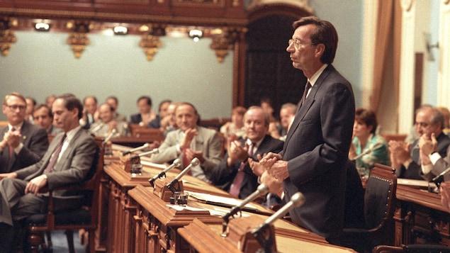 Robert Bourassa, debout, est applaudi par les membres de l'Assemblée nationale du Québec le 22 juin 1990.