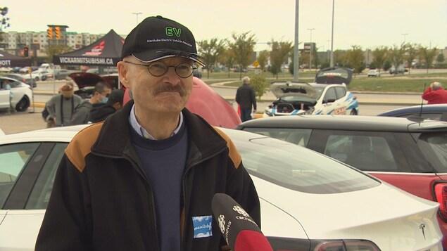 Robert Elms est dans un stationnement, entouré de voitures.