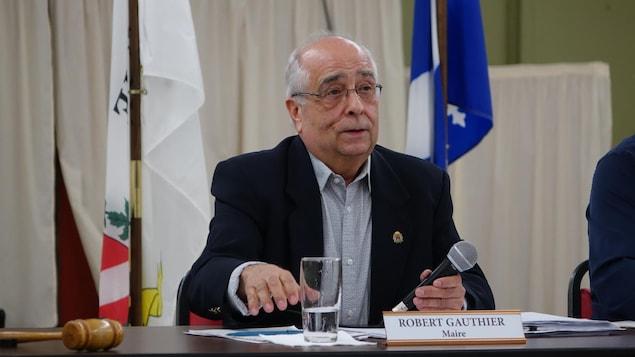 Le maire assis devant une insigne qui dit son nom