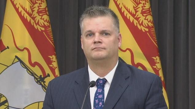 Robert Gauvin, avec des drapeaux du Nouveau-Brunswick en arrière-plan