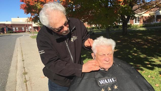 Robert Lévesque coupe les cheveux de son père Gérald, lui-même un ancien barbier, à l'extérieur du foyers de soins où il réside.