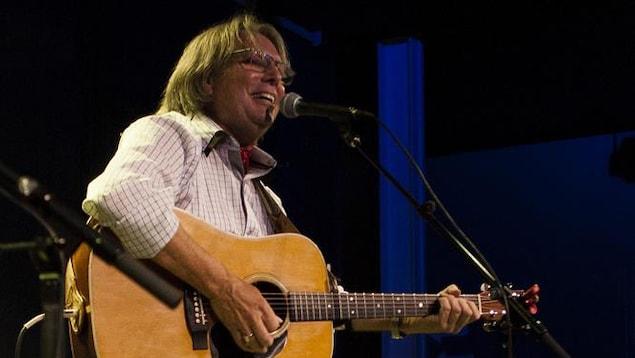 Robert Paquette en concert avec sa guitare.