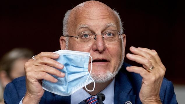 Le Dr Robert Redfield s'adresse aux sénateurs en tenant un masque à la hauteur de son visage.