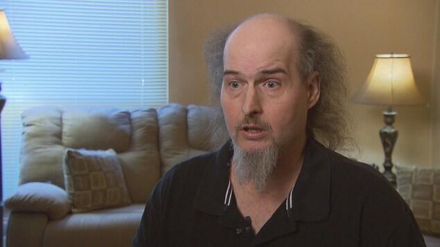 Un homme aux cheveux ébouriffés gris et une petite barbichette