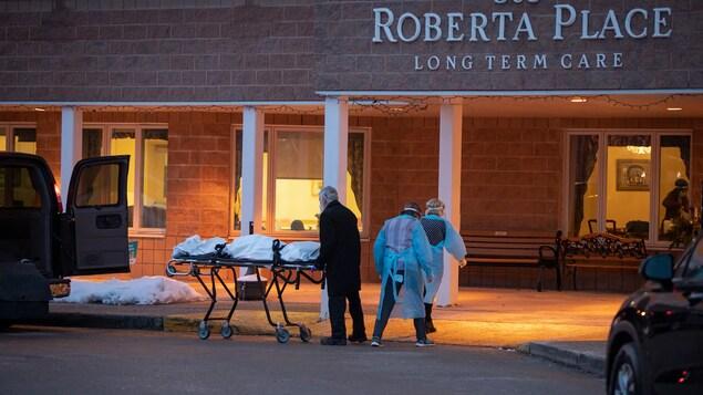 Un homme pousse une civière devant un centre de soins de longue durée.