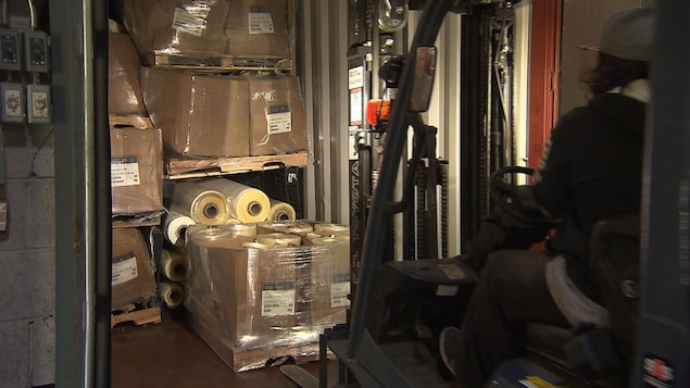Un chariot élévateur charge le ballot de plastique dans un camion.