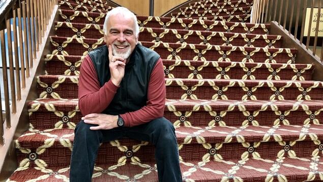 Robin Doucet, directeur général du Salon du livre de Rimouski, assis dans les escaliers et souriant à l'appareil photo.