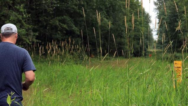 Un homme de dos marche sur sa terre en Colombie-Britannique.