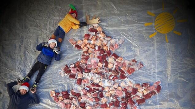 Jonathan Bélanger prend la pose avec ses deux jeunes garçons et les paquets de viande, placés en forme de sapin de Noël.
