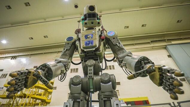 Vue en contre plongée du robot qui semble vouloir attraper l'objectif de l'appareil photo.