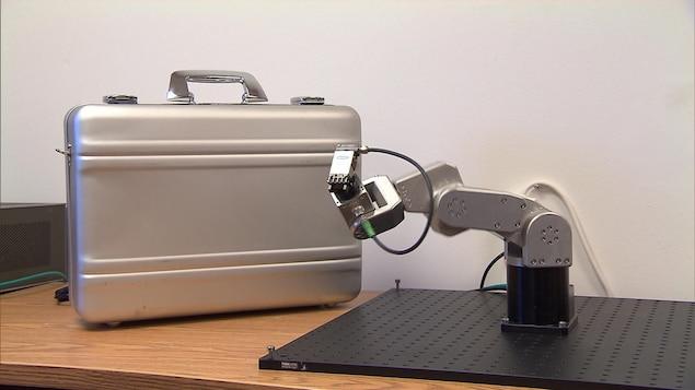Le petit bras robotisé de Mecademic à côté d'un bagage de cabine