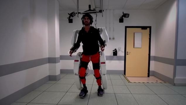 Un homme marche grâce à un exosquelette fixé au plafond, attaché à ses pieds et à ses mains.