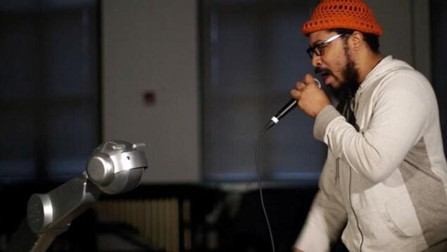Un robot doté d'un visage humanoïde sur un bras mécanique regarde un rappeur chanter dans un micro.