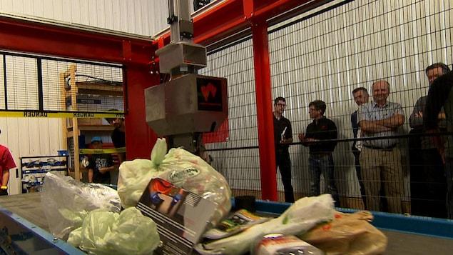 Le bras articulé du robot créé par Waste Robotics trie les sacs remplis de restes de table.