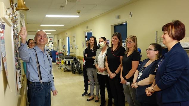 Roch Gaudreau debout, tire sur la corde d'une cloche, dans un couloir d'un département d'hôpital, avec des employées qui le regardent, souriantes.