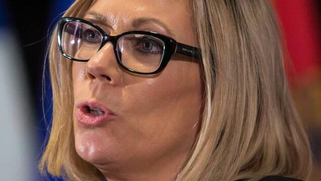 Un plan rapproché du visage d'une femme blonde avec des lunettes.