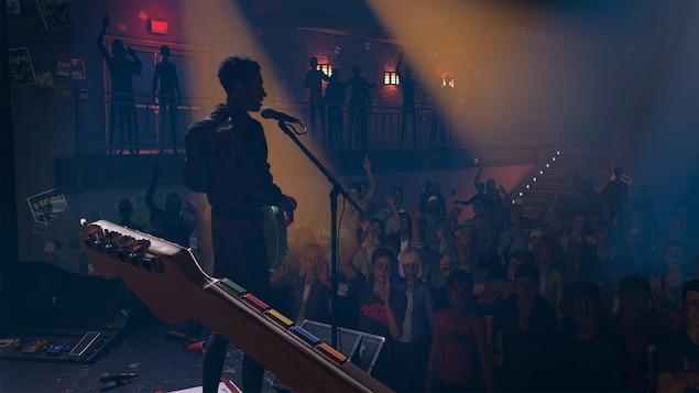 Un groupe de musique joue devant une foule dans une salle de concert et on voit les cinq boutons de couleurs traditionnels de Rock Band remplaçant les cordes sur le manche de guitare.
