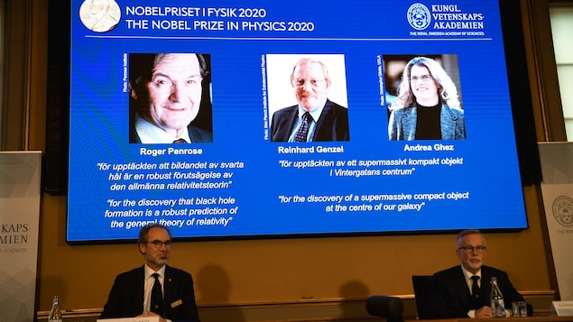 Deux homme sont assis à un table et la photo des trois lauréats est projetée au-dessus d'eux sur un écran.