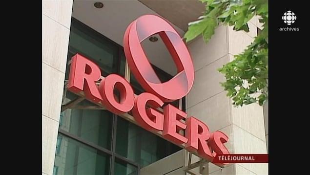 Enseigne avec l'insigne et le logo de Rogers devant le bâtiment de son siège, à Montréal.