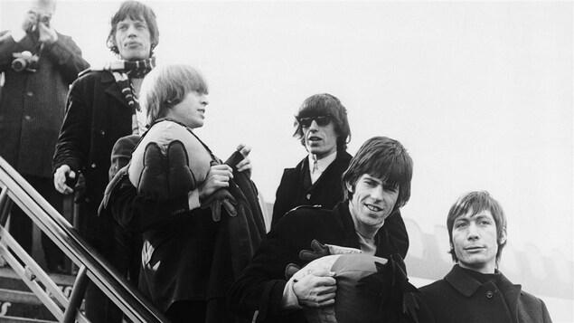 Les Rolling Stones débarquent d'un avion.