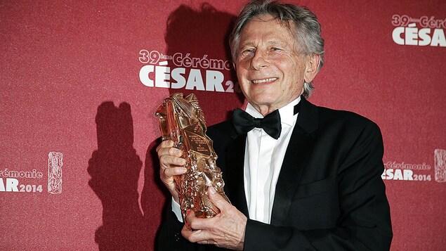 L'homme tient un trophée.