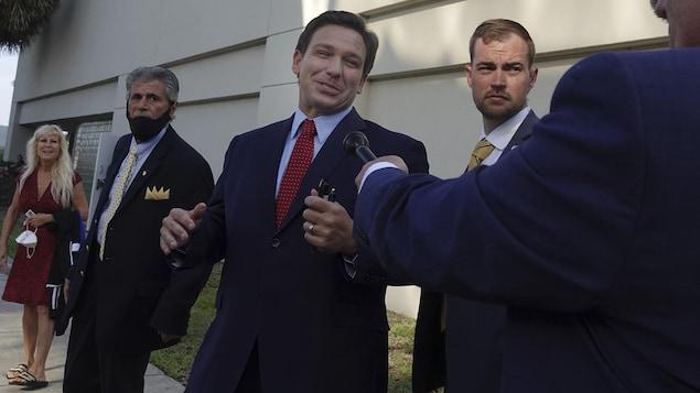 Ron DeSantis, à l'extérieur, tourné vers un homme tenant un microphone et entouré de deux collaborateurs.