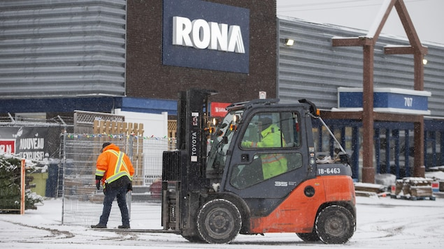 Un homme conduit un chariot élévateur devant un magasin Rona.