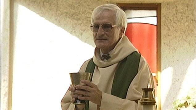 Un homme d'un certain âge porte une soutane. Il a un calice dans les mains.