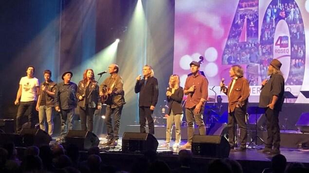 Une douzaine d'artistes chantent en coeur du scène.