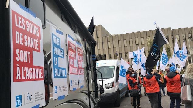 Des manifestants devant la roulotte du FIQ.