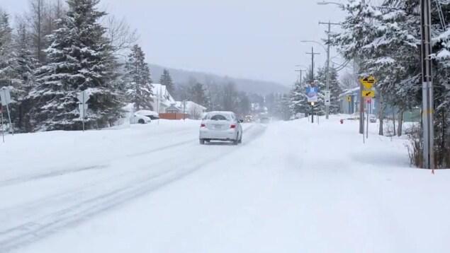 Une voiture sur une route enneigée.