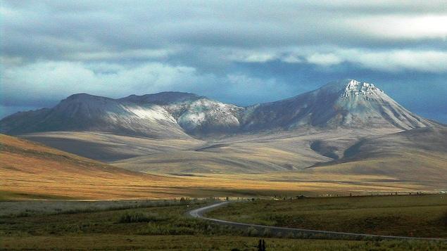 Plan large de la route avec au fond les montagnes aux sommets enneigés