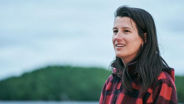 Une femme portant un veste à carreau regarde vers sa droite, avec une forêt et de l'eau en arrière-plan.