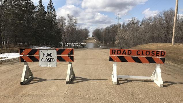 Des barrières orange bloquent une route inondée.
