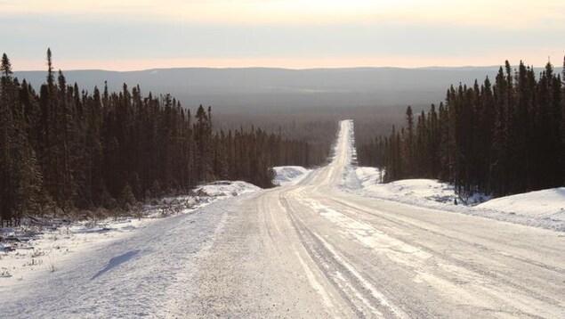 Prise de vue sur la route Translabradorienne traversant la forêt en hiver.