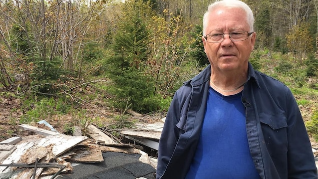 Jacques Roy debout devant des déchets en forêt