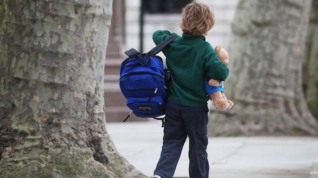 Un jeune garçon marche avec son sac d'école en main et sa peluche dans l'autre.