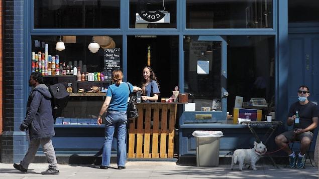 Des gens dans une rue à Londres devant un comptoir-restaurant.