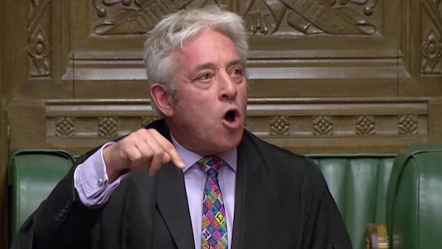 Un homme au cheveux blancs vêtu d'un complet noir porte une cravate très colorée.