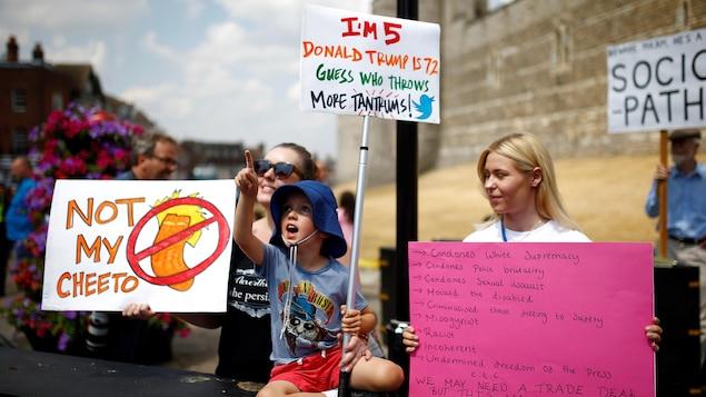 Un enfant pointant quelque chose du doigt, entre deux manifestantes tenant des pancartes.