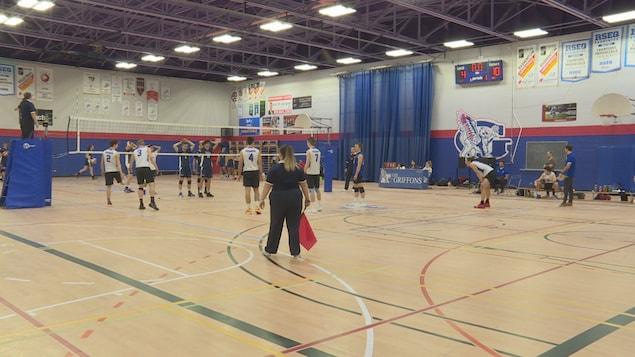 Des joueurs de volleyball de part et d'autre d'un filet lors d'un match dans un gymnase.