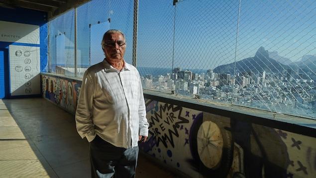 Rubem César Fernandes devant une fenêtre qui surplombe la ville de Rio de Janeiro, au Brésil.