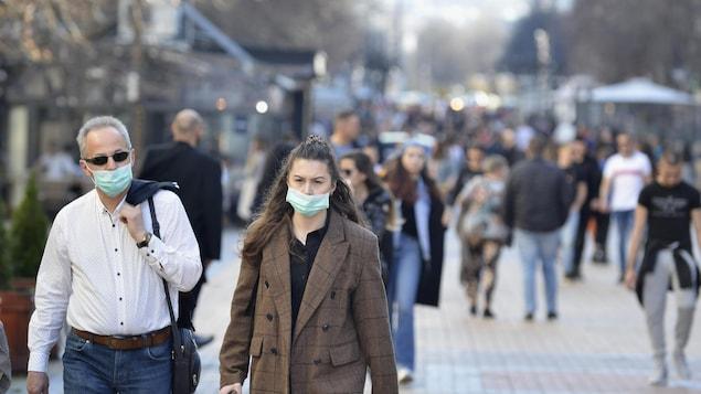 Un homme et une femme portant des masques marchent dans la rue.