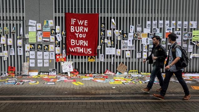 Deux hommes passent devant un mur recouvert d'affiches et de photos. Sur un drap suspendu, on peut lire : If we burn, you burn with us. (Si nous brûlons, vous brûlez avec nous.)