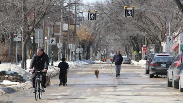Une rue fermée à la circulation automobile. Les gens y font du vélo ou promènent leur chien, deux enfants discutent.