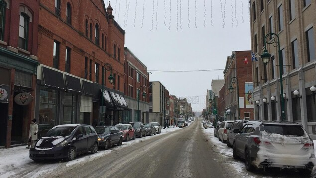 La rue Wellington Nord au centre-ville de Sherbrooke en hiver. Des voitures sont stationnés de chaque côté de la rue.