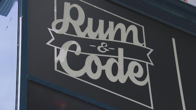 Sur un fond noir, à l'extérieur d'un édifice, on peut lire : Rum and Code.